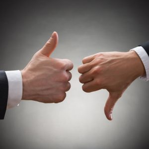 40870643 - close-up of two businesspeople hands showing thumb up and thumb down sign